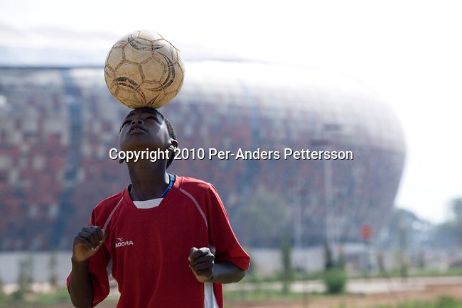 JOHANNESBURG,SOUTH AFRICA -JANUARY16:A soccer player in a youth teampracticeon a field in front of Soccer CityonJanuary16, 2010,in Johannesburg, South Africa.This young player practiceseveral times a week and usually have at least one game on the weekend. His team is based inSowetoand they are struggling with funding for uniforms and balls. Soccer City is the stadium where the opening and final game of the World Cup will be played. Many soccer fans in the country are excited about the upcoming World Cup tournament in June, 2010.(Photo by Per-AndersPettersson/GettyImages)
