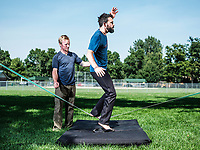 Owner of Rocky Mountain Slackline Dakota Collins (left), works with The Adventurist columnist, Clint Carter at Spring Park in Ft. Collins, Colorado, Sunday, August 27, 2017. Carter take on a vertigo-inducing highline that stretches across a traverse after only 4 days of training.<br /> <br /> Photo by Matt Nager
