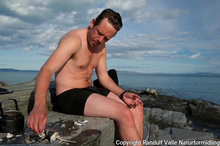 Seimølje på svaberget en sommerdag. ---- A meal of fish prepared on the rocks by the shore.