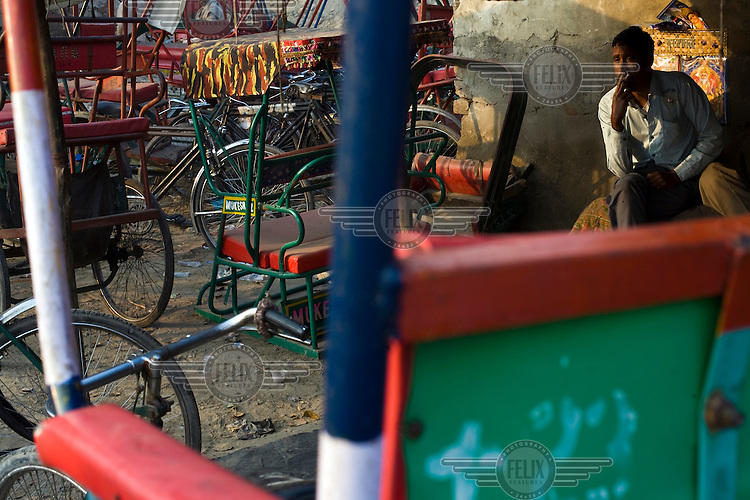 Homeless rickshaw drivers smoke and relax at a tea stall in a parking lot next to the Yamuna River where they sleep.