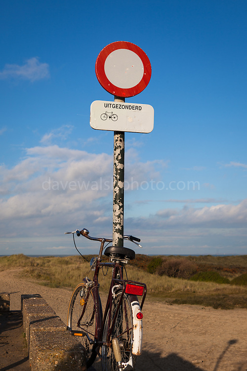 """Bicycle on the beach at Zwin Nature Reserve, Knokke, Flanders, Belgium. Sign reads """"uitgezonderd"""" - """"except"""""""