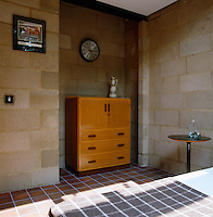 A clock by Robert Welch and a 1930's cabinet sit in an alcove in this bedroom with exposed brick walls and a tiled floor