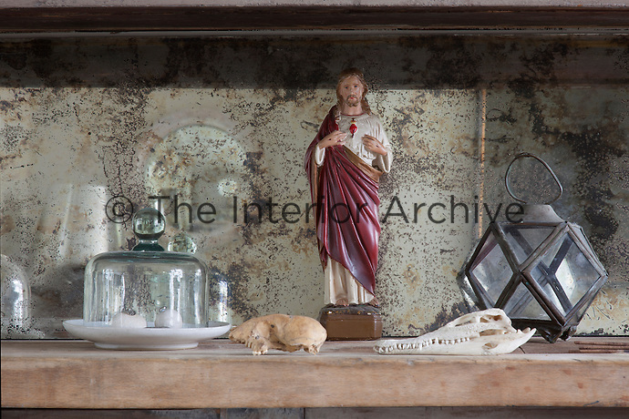 Detail of a tiny Jesus figurine standing among other objects, including a baby crocodile scull, on the dining room sideboard