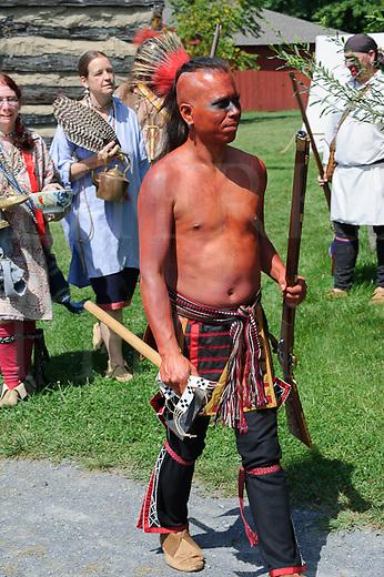 Native American Indian reenactor in costume and rifle, walking.