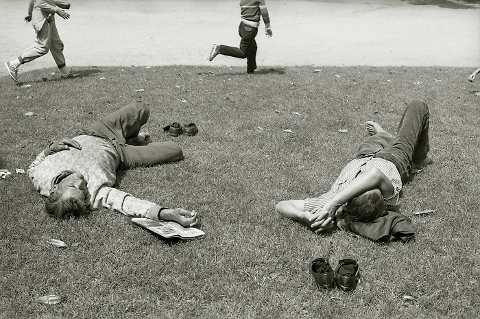 Children run past two men sleeping on the grass in a public park in Barcelona. Spain 1985.