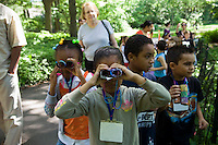 First grade students from PS 14X go birding in Central Park in New York on Thursday, May 20, 2010. The students participate in LeAp's Active Learning Leads to Literacy Program,  a program that teachers literacy through the arts. The students hand crafted their binoculars out of toilet paper tubes.   (© Frances M. Roberts)