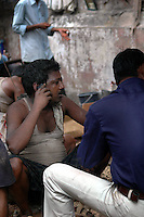 An Indian labour using a mobile phone on a road of  Kolkata, West Bengal,  India  7/18/2007.  Arindam Mukherjee/Landov