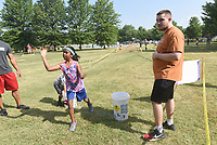"""NWA Democrat-Gazette/FLIP PUTTHOFF <br /> OBSTACLE RUNAROUND<br /> Christian Lane (right) helps runners on Saturday June 9 2018 at the water balloon toss during the Obstacle Runaround at the Jones Center for Families in Springdale. Youngsters age 5-12 took part in the run with 15 obstacles on the course including a slip and slide, belly crawl, and mazes. """"It's our version of a mud run for kids,"""" said Stephen Paul with the Jones Center."""