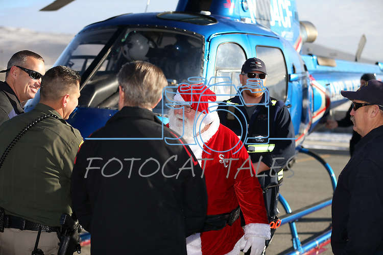 Event organizers greet Santa after he arrives on a Careflight helicopter at the 11th annual Holiday with a Hero at Walmart in Carson City, Nev., on Wednesday, Dec. 16, 2015. <br /> Photo by Cathleen Allison