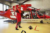 "Switzerland. Canton Ticino. Locarno Airport LSZL. The Rega base's official name is Locarno LSMO AFB (Rega 6).  Alarm triggering device for rescue operation. The Doctor Michele Musiari rushes to dress waterproof pants and a pair of mountain shoes. 10 minutes is the maximum time to get ready before take off of Rega Agusta AW109 SP Grand ""Da Vinci"" helicopter. All Rega helicopters carry a crew of three: a pilot, an emergency physician, and a paramedic who is also trained to assist the pilot for radio communication, navigation, terrain/object avoidance, and winch operations. The name Rega was created by combining letters from the name ""Swiss Air Rescue Guard"" as it was written in German (Schweizerische Rettungsflugwacht), French (Garde Aérienne Suisse de Sauvetage), and Italian (Guardia Aerea Svizzera di Soccorso). Rega is a private, non-profit air rescue service that provides emergency medical assistance in Switzerland. Rega mainly assists with mountain rescues, though it will also operate in other terrains when needed, most notably during life-threatening emergencies. As a non-profit foundation, Rega does not receive financial assistance from any government. The AgustaWestland AW109 is a lightweight, twin-engine, helicopter built by the Italian manufacturer Leonardo S.p.A. (formerly AgustaWestland, Leonardo-Finmeccanica and Finmeccanica). Leonardo S.p.A is an Italian global high-tech company and one of the key players in aerospace. In close collaboration with the manufacturer, the Da Vinci has been specially designed to cater for Rega's particular requirements as regards carrying out operations in the mountains. It optimally fulfills the high demands made of it in terms of flying characteristics, emergency medical equipment and maintenance. Safety, performance and space have been increased, and maintenance and noise emissions reduced. 9.09.2017 © 2017 Didier Ruef"