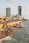 School children paddle in the sea on small sandy beach at Galle Face Green, Colombo, Sri Lanka, Asia