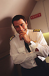 "John Travolta, captain and pilot of his own jumbo jet, has a laugh and smile during the photo-shoot inside his plane...John Travolta is pilot of his very own jumbo jet, a 1964 Boeing 707-100 series. In 2003, John Travolta flew his jumbo jet around the world, in partnership with Quantas, to rekindle confidence in commercial aviation, and to remind us that elegance and style are a part of flying. The crew are dressed in tailor made authentic uniforms from the Quantas museum. The men's uniforms are styled on British Naval uniforms and the ladies' designed by Chanel. His jumbo jet sports a personalised number plate N707JT which speaks for itself. The aircraft is named ""Jett Clipper Ella"" dedicated to his son and daughter. This jumbo together with his other aircraft are housed in purpose built hangars at his home in Florida, USA."