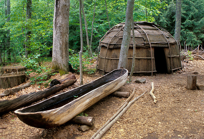Bark covered wigwam and a dug out canoe in the woodlands setting of an Indian village in the Northeast.