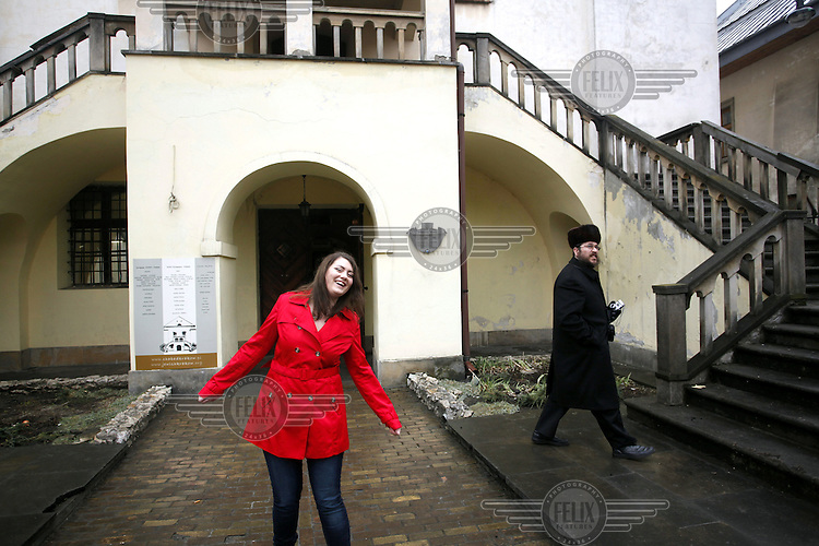 "Oliwia Dabrowska, 24, who played the little girl in a red coat in Steven Spielberg's 1993 film ""Schindler's List"", poses in the courtyard of the Isaac synagogue in the Kazimierz district, the former Jewish quarters of Krakow. The hasidic jew on the picture is a tourists. Dabrowska was advised by Spielberg not to watch the film until she is 18 years old but she decided to watch it when she was 11 and was very distressed at the time. ."