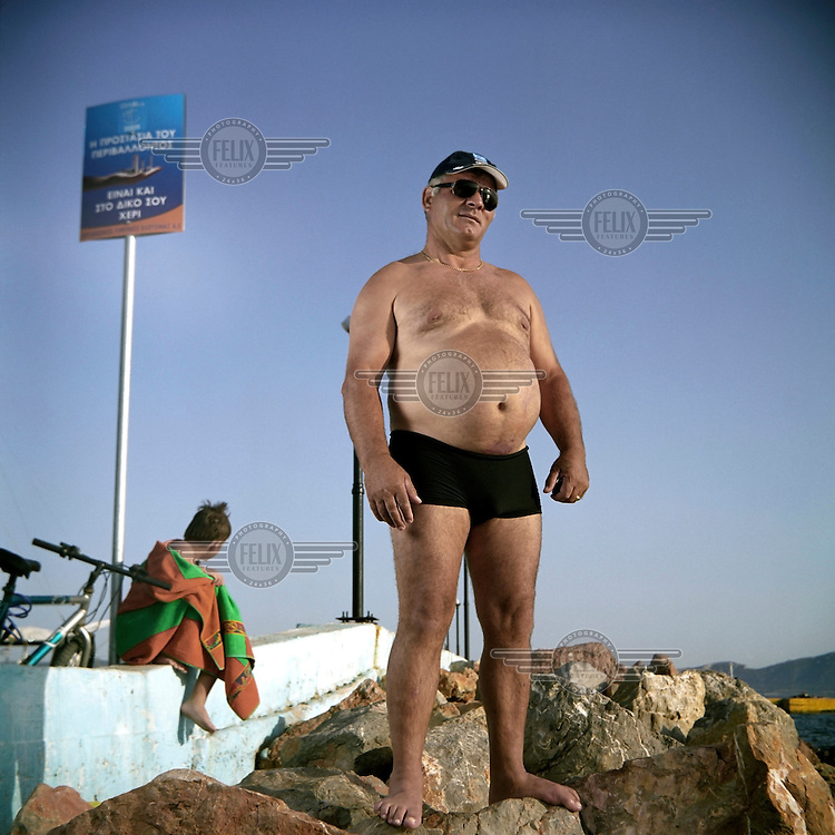 Albanian Valentino stands on rocks beside the sea in Elefsina. The water around the town is not safe for swimmers as it is heavily polluted by waste from nearby shipyards, oil refineries, cement factories and tanneries.