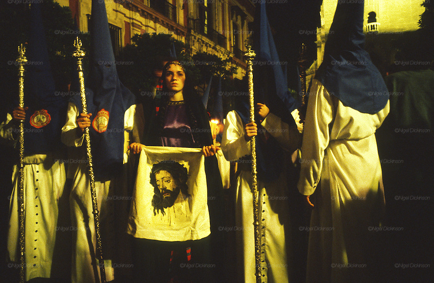 "Hermandad de Sagrada Mortaja, Seville, Semana Santa, Andalusia, Spain..Semana Santa de Sevilla, Catholic Holy Week from Palm Sunday to Easter Sunday, is one of the most important traditional, cultural and spiritual events in Seville. The origins of the penitential Holy Week in Seville are to be found in the late Middle Ages. At the heart of Semana Santa are the brotherhoods (Hermandades y Cofradias de Penitencia).  At the centre of each procession are the pasos, an image or set of images set atop a movable float of wood. When a brotherhood has three pasos, the first one would be a sculpted scene of the Passion or an allegorical scene, known as a misterio (mystery); the second an image of Christ and the third an image of the Virgin Mary known as a dolorosa. Many sculptures are of great antiquity and considered artistic masterpieces. A total of 60 penitential processions are organized by hermandades and cofradías, religious brotherhoods. Members precede the pasos dressed in penitential robes and hoods. Sometimes accompanied by brass bands. They take designated routes from home churches and chapels to the Cathedral and back again. Improvised flamenco songs ""saetas"" are sung to the processions from balconies. The marchers are often accompanied by brass bands, cappella choirs, or a drum and trumpet (historical traditions for a poorer neighborhood)"