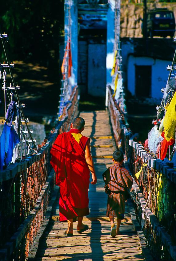 Monks crossing bridge at the Punakha Dzong, Punakha Valley, Bhutan.
