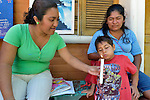 Ana Laura Cabrera Hernandez holds a candle for a boy to blow out during a session of the early intervention program of Piña Palmera, a center for community based rehabilitation for people living with disabilities in Zipolite, a town in Oaxaca, Mexico. Cabrera is a trainer at the center.