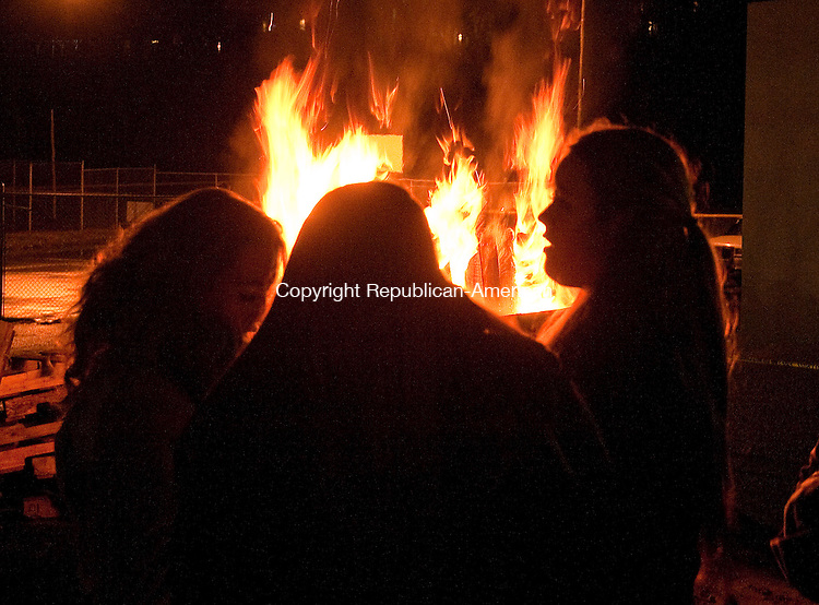 THOMASTON, CT--- -112815JS06--A group of girls keep warm in front of the bonfire in the JDT's Brickhouse parking lot during the annual Light Up Thomaston event Saturday in downtown Thomaston. <br /> Jim Shannon Republican-American