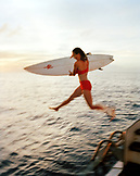 FIJI, Northern Lau Islands, a woman jumps off of a yacht with her surfboard, Southern Pacific Ocean