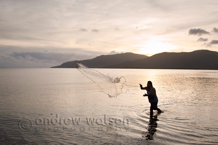 Man casting a net on the Esplanade at dawn.  Cairns, Queensland, Australia
