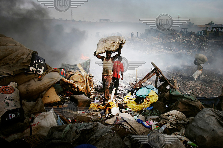 Scavengers at the Olusosun landfill site. The Olusosun dump is Nigeria's largest trash heap comprising over 100 acres of garbage and is believed to be the largest in Africa. There are around a thousand houses built within its boundaries.