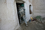 A U.S. soldier from Company C, 1st Battalion, 12th Infantry Regiment enters a house looking for Taliban weapons in the village of Pashmul, in Zhari district, Kandahar province, Afghanistan. President Obama is expected to announce up to 35,000 more troops for Afghanistan in coming weeks. Most of them will likely be deployed in Kandahar and other southern provinces in an effort to stem the worsening Taliban insurgency. Nov. 24, 2009. DREW BROWN/STARS AND STRIPES