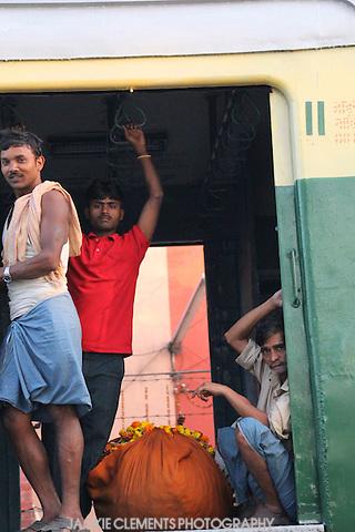 Three men take a suburban train through Kolkata.