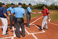 Ball State Cardinals head coach Rich Maloney (2) shakes hands with umpire Gary Rosplohowski during the lineup exchange before a game against the Mount St. Mary's Mountaineers on March 9, 2019 at North Charlotte Regional Park in Port Charlotte, Florida.  Also shown (clockwise) home plate umpire Phil Pupillo, Mountaineers head coach Scott Thomson, and third base umpire Kyle Travis.  Ball State defeated Mount St. Mary's 12-9.  (Mike Janes/Four Seam Images)