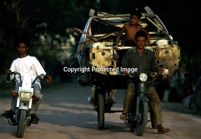 A father and son transporting an old car on a carriage on March 11, 1998 in central Phnom Penh, Cambodia. Cambodia is one of the poorest countries in the world and are struggling to lose the ghosts from the Khmer Rouge Era. The United Nations backed elections in 1992. .(Photo: Per-Anders Pettersson/ Liaison Agency)