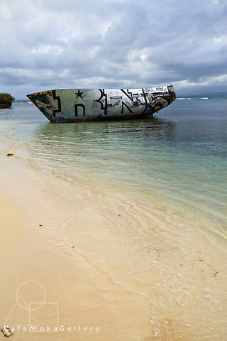 A wreck painted with graffiti on the sandy beach on the Ilet de Gosier