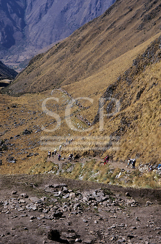 Inca Trail, Peru. View down Llulucha valley with dusty area in foreground and trail with line of hikers behind.