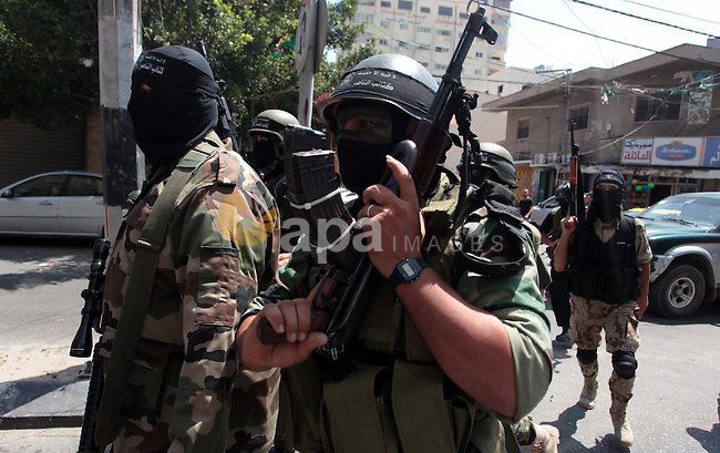 Palestinian militants of the Nasser Salah al-Din Brigades the military wing of the Popular Resistance Committees take part in a press conferenceon on cross-border escalation between Palestinians and Israel, in Gaza City July 5, 2014. With Israel having mobilised ground forces outside Gaza on Thursday in a threat to invade, Egypt tried to mediate a truce. Israel and the Islamist Palestinian Hamas movement each said the other had to back down first. Photo by Ashraf Amra