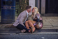 Saturday  17 December 2016<br /> Pictured: A couple kiss on the pavement on Swansea's Wind Street <br /> Re: Swansea City Centre and the notorious Wind street, often nicknamed 'Wine Street' is packed full of Christmas jumpers and glitzy dresses as thousands head to office dos across the UK in the biggest party night of the year.