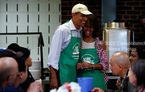 United States President Barack Obama and his daughter Malia honor the Martin Luther King, Jr. legacy by serving meals to the needy at.So Others Might Eat (SOME), a soup kitchen/homeless service provider, in Northwest Washington, D.C., Monday, January 18, 2010. Michelle Obama and other daughter Sasha (unseen) were also with them..Credit: Aude Guerrucci / Pool via CNP