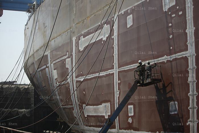 Shipyard workers examine the exterior hull of a ship at the Dalian shipyard in Dalian, Liaonin Province, China, on April 23, 2011. China's shipping industry is expected to make a strong recovery as over capacity is smaller than expected and China's demand for raw materials needs more ships to transport them.