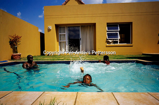 Oscar Dube, a young successful black man takes dip in the pool with his daughter's cousins on March 25, 2002 in Johannesburg, South Africa. Oscar works for the Swedish mobile phone and equipment maker. A growing number of people belong to the new black elite in the country. Well educated and connected, they have risen from the poverty in the townships to a very different lifestyle, since the fall of Apartheid and the start of democracy in the country in 1994.