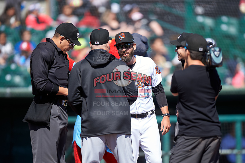 Inland Empire 66ers manager Ryan Barba (6) meets with Modesto Nuts manager Denny Hocking (23) and umpires Anthony Warner and Harrison Silverman during a pregame meeting before a California League game between the 66ers and the Nuts on April 10, 2019 at San Manuel Stadium in San Bernardino, California. Inland Empire defeated Modesto 5-4 in 13 innings. (Zachary Lucy/Four Seam Images)