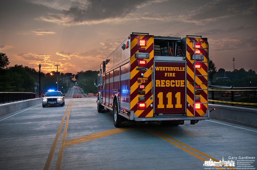 A Westerville police car and fire truck sit on the Main Street Bridge at sunrise to mark the official opening of the new structure after a year of work to replace the old bridge.