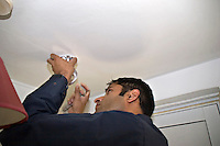 Firefighter installing a domestic smoke detector as part of their community fire safety campaign Oxfordshire UK. This image may only be used to portray the subject in a positive manner..©shoutpictures.com..john@shoutpictures.com