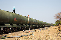 A man walks across the top of the 'water train' of Latur which delivers millions of litres of water to the city from over 200 miles away in the west of the country. Even with the train arriving each day to replenish government water stores, it is still not enough to supply water to all of Latur's half a million residents.