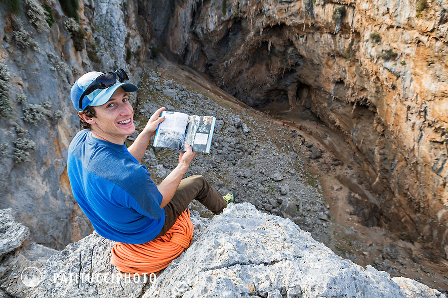 A climber sitting on the rim of the Sikati Cave, looks at his guidebook. Kalymnos, Greece.
