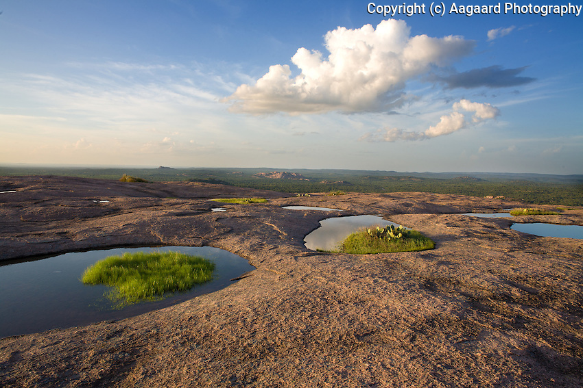 After a rain, these vernal pools form on the summit of Enchanted Rock.  This afternoon I was fortunate and found a cloud formation that complemented the foreground.  Visible on the horizon is Bullhead Mountain; closer to the middle is Watch Mountain.<br /> <br /> Canon EOS 5D, 24mm f/2.8 lens