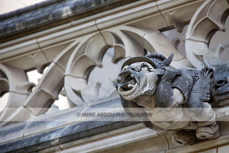 "This gargoyle was carved in honor of the Washington National Cathedral's ""Master Carver.""  The gargoyle holds onto his hat to avoid ""blowing his top,"" which the Master Carver was known to do.  The Washington National Cathedral in Washington, DC is home to more than 200 stone-carved gargoyles.  The purpose of the gargoyles were to both keep evil out of the cathedral and to serve as a water drainage system in torrential rain - the water pours out of the mouth of the gargoyle."