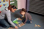 Educaton preschool 4-5 year olds female volunteer student teacher working with child on puzzle activity horizontal