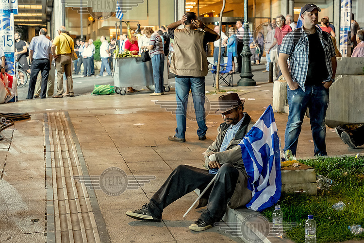 ATHENS, GREECE: a few days before general elections, a man who assisted to a Nea Demokratia meeting rests holding a greek flag.