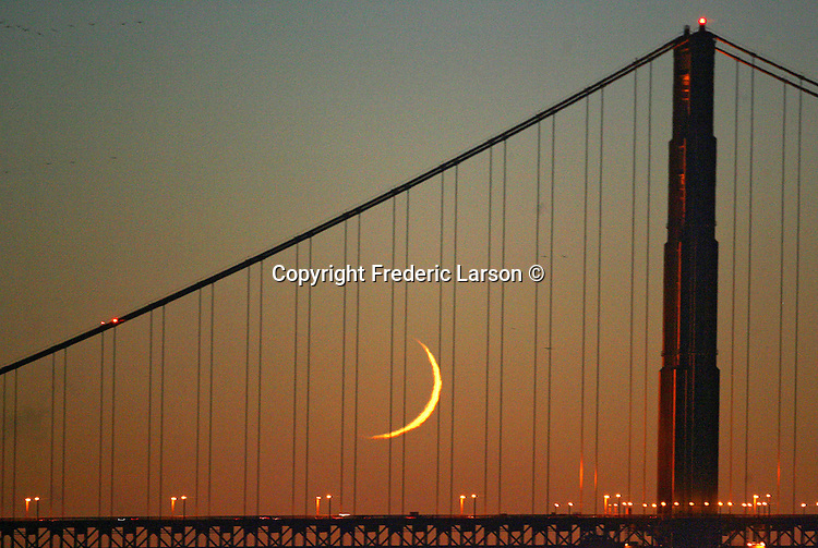 A thin crescent moon found a resting spot during the evening twilight between the cables near the south tower of the Golden Gate Bridge which was viewed from Fisherman Wharf.