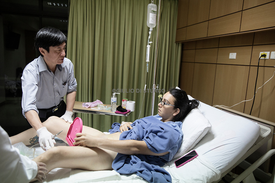 """Dr Suporn Watanyusakul shows patient Olivia Thomas her new vagina after gender reassignment surgery at a hospital in Chonburi, near Bangkok, Thailand.<br /> <br /> Olivia Thomas, 38, started to take hormones on November 20, 2009.<br /> <br /> When Olivia was still living as a man he was married with Andrea and he had a daughter.<br /> <br /> """"I knew I was different from a very early age, around age 9. I believed doctors had surgically given me the wrong parts at birth. However, as I was told I was a boy by my parents, that is what I believed. As a teenager, I started dressing in women's clothes and wondered what it would be like to have a female body and breasts. I repressed these thoughts and feelings through my twenties, and it wasn't until I was nearly thirty that I realized I was transgender. I was married at that time and had a newly born daughter. I then started my transition in earnest, going through the process of coming out to family, then friends, then my work. I found acceptance from many friends and work colleagues, but some family members were and continue to be resistant to my transition. After starting hormones in November 2009, I had Facial Feminization Surgery (FFS) in November 2012 with Dr. Mark Zukowski in Chicago, Illinois, USA. Finally, on January 30, 2017, I was able to have Gender Reassignment Surgery (GRS) with Dr. Suporn in Chon Buri, Thailand.<br /> <br /> She is currently working in the motorcycle industry as a repair technician."""