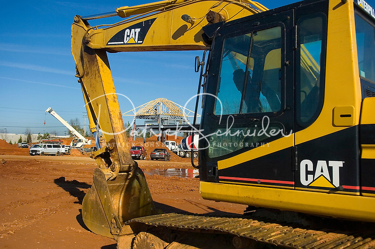 02/22/07:  The arm of a Cat backhoe frames a construction project during expansion/construction of a Charlotte-area shopping center. Charlotte, NC, is one of the country's fastest-growing cities. ..By Patrick Schneider- Patrick Schneider Photography.