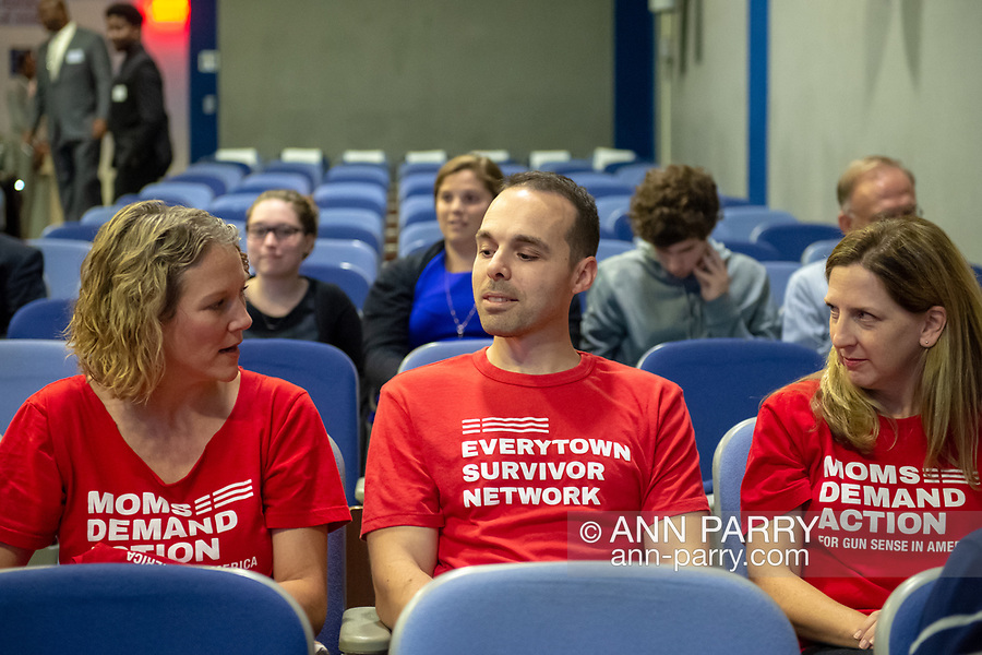 Hempstead New York, October 5, 2018. Man at center, a Long Island survivor of the Oct. 1, 2017 Las Vegas shooting is wearing EVERYTOWN SURVIVOR NETWORK shirt and is sitting between two woman wearing MOMS DEMAND ACTION for Gun Sense in America red shirts. They arrived early for Sen. Gillibrand's Town Hall at Hofstra, Long Island.